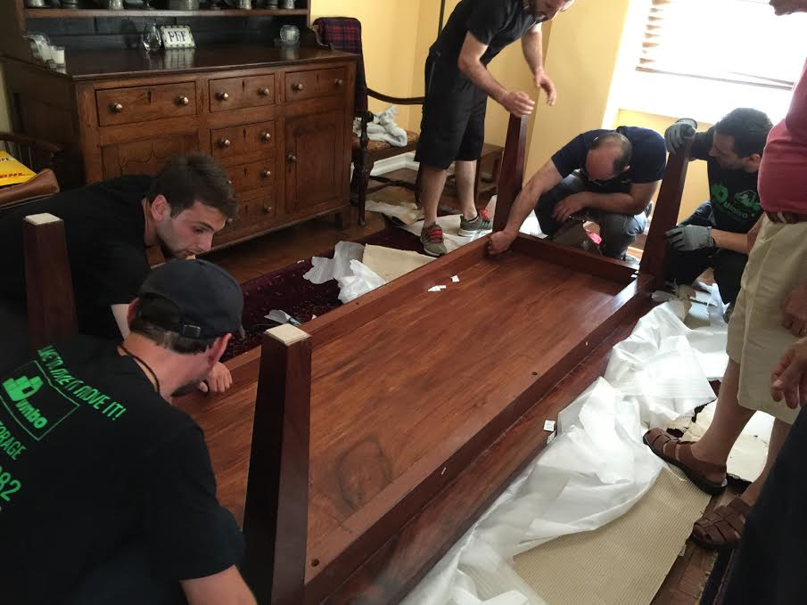 Movers Disassembling A Desk