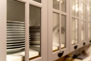 a beige china cabinet with glass doors