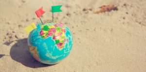 Plastic Earth model in sand - pick any place on the globe where you want to move