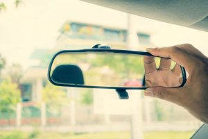 A Driver Is Adjusting A Rear-view Mirror