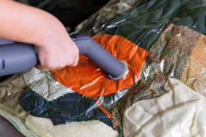 A Girl Is Packing Clothes In A Vacuum Bag
