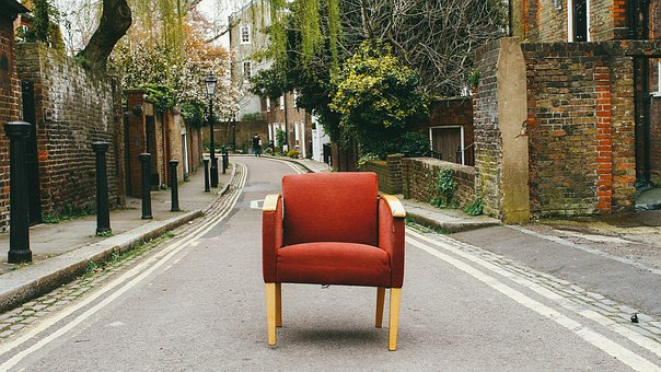 brown armchair on the street awaiting for couch disposal NYC professionals