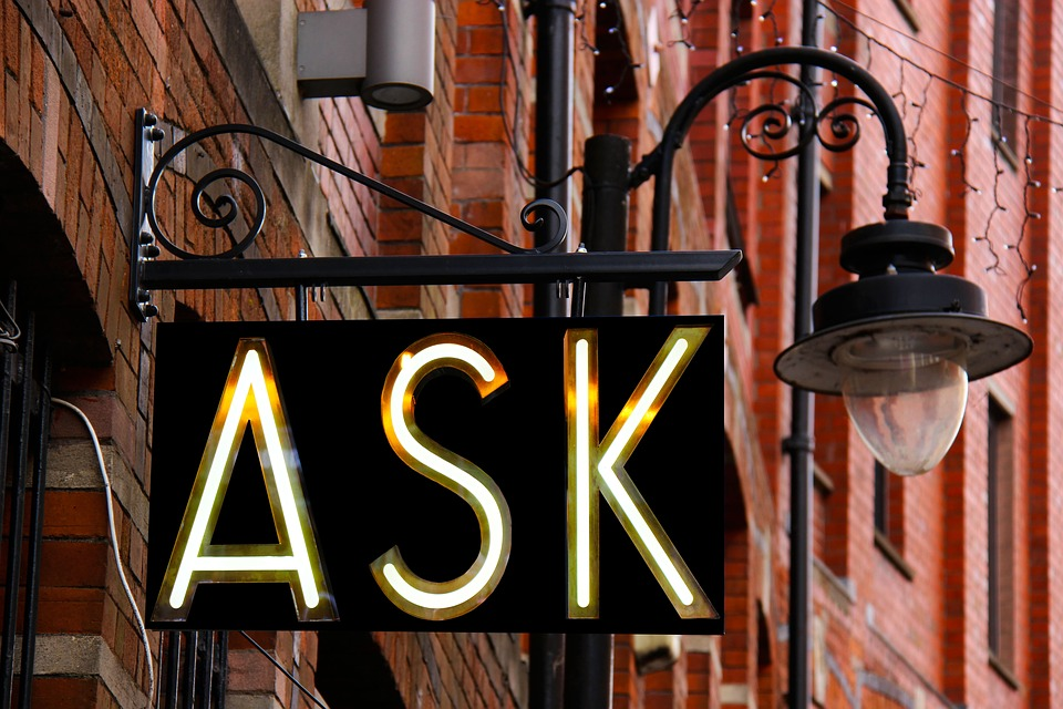 An ask sign hanging on a wall.
