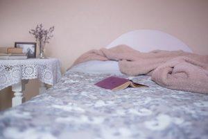 a bed with a blanket and a book