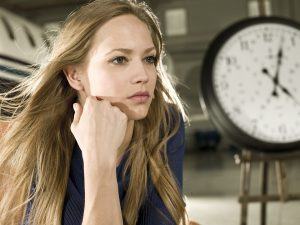 a concerned girl sitting near the clock and thinking about how to move house
