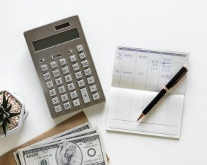 calculator, pen, paper and money on the table