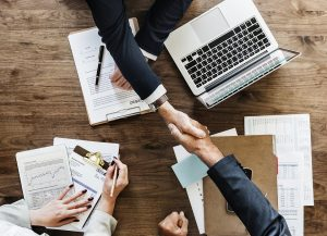 Two shaking hands over a desk with documents and a laptop suggesting choosing a good moving company avoiding making moving mistakes