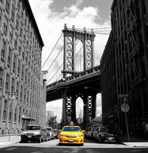 a yellow cab between buildings and a Manhattan bridge in the background