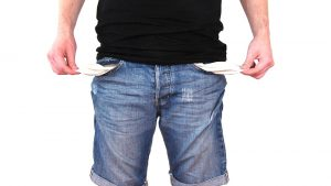 a man in jeans pulling out his empty pockets