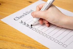 A white checklist with a few checked boxes and a white pen