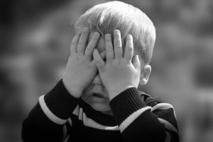 a toddler covering his eyes with hands