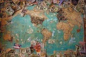 Image of a world map with dollar bills on its sides
