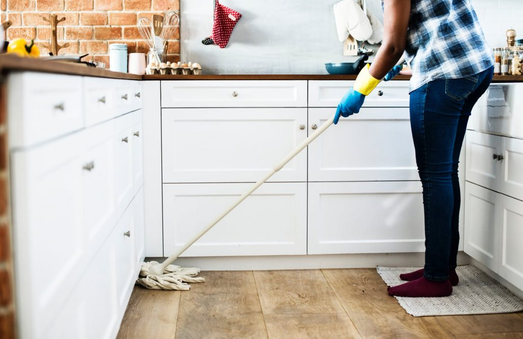 person using a mop in the kitchen