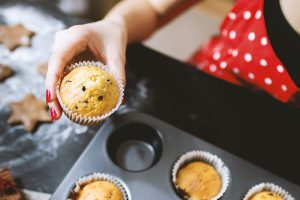 A woman holding a homemade muffin in the muffin cup