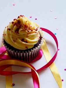 a chocolate cupcake with white and yellow ribbons served at a housewarming party