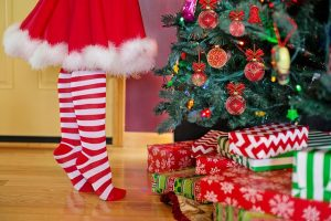 girl next to the Christmas tree with presents