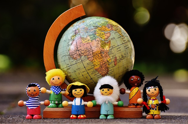 Image of a globe with toys representing people right next to it