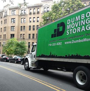 Green ''Dumbo moving and storage'' truck on the road helping the customer relocate abroad