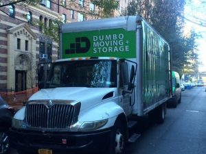 green and white dumbo moving and storage moving truck on the street