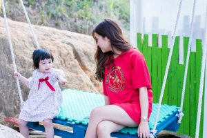 mother in red dress and daughter sitting on swing bench and talking about the move