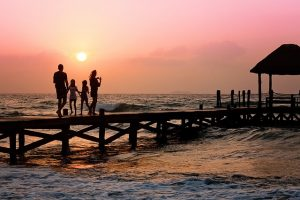 Family of four walking down the pier - considering relocating after you retire