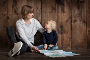 Mother and child sitting in front of a map and talking about the household relocation