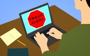 fraud alert sign on a laptop placed on a desk in front of a man looking for the information about a cheap move