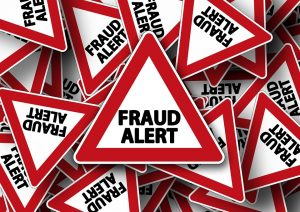 a lot of red and white fraud alert road signs