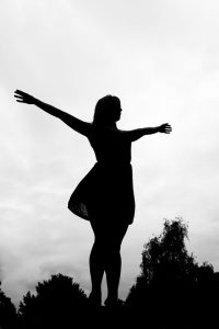 a woman silhouette breathing and raising her arms