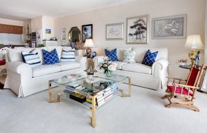 Two white sofas with blue and white decorative pillows, paintings on walls and a glass coffee table can make your new place feel inviting after moving to NYC