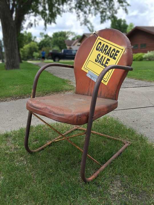 an old metal chair with a garage sale sign on it