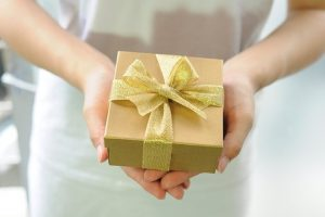 a gild holding a small yellow gift box