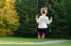 a girl in whit on the swing in the park after moving to the suburbs