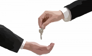 A hand giving a key to another hand before moving out of a rental