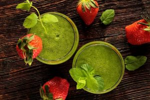 two green smoothies with strawberries around