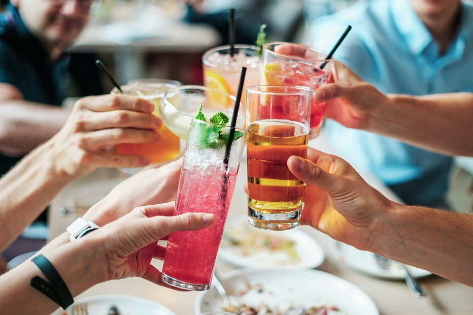 a group of people making a toast with their drinks
