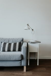 grey sofa with a cushion and a lamp on a table