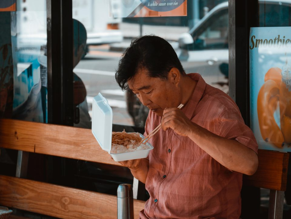 A man eating Chinese food