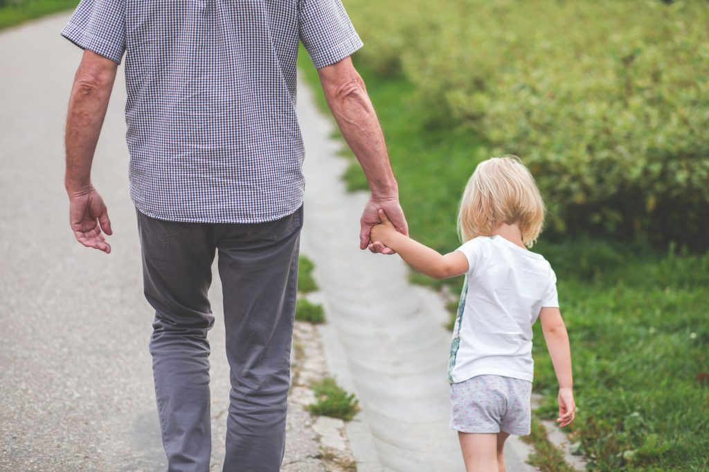 a father walking with a kid