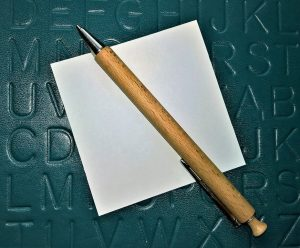 an empty piece of a paper with a pen on a green surface
