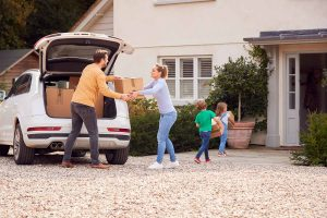 A Family Loading A Car For Moving