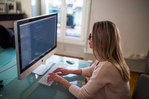 woman sitting in front of the pc and researching job options before moving for love