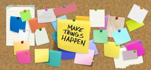 sticky notes with a message ''make things happen'' pinned to a corkboard as a reminder for an upcoming office move