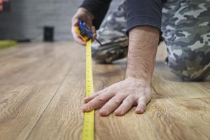 A man measures his home office with a measuring tape