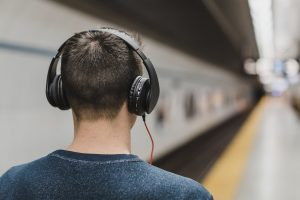 man with headphones at a blurred metro station