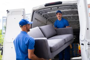 Movers Loading A Couch Into The Moving Van