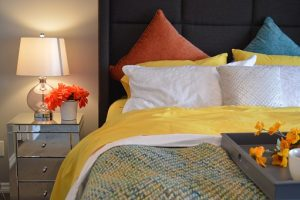 king-size bed with colorful pillows and a night stand