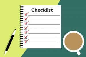 moving checklist with a cup of coffee and a pen on a green background