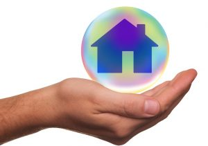 a hand holding a home model in a blue bubble