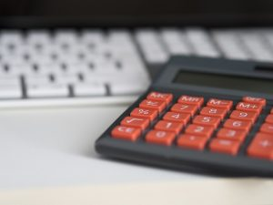 calculator with red buttons on a desk near the pc keyboard